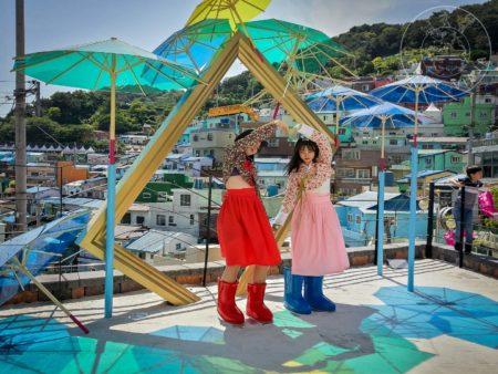 Coreanas posando en escultura interactiva de parasoles y retrato
