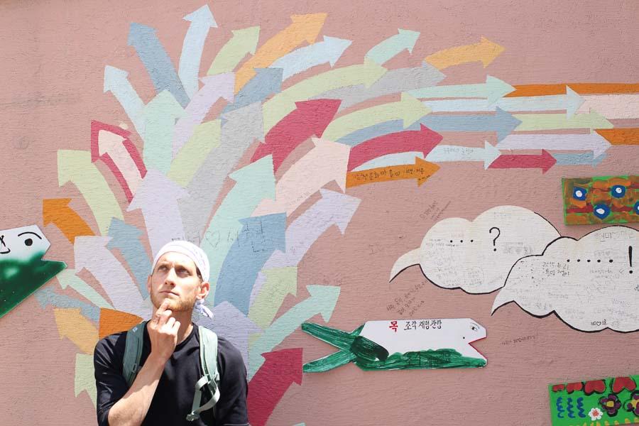 Diego pensativo en un bello mural de gamcheon village en su festival anual.