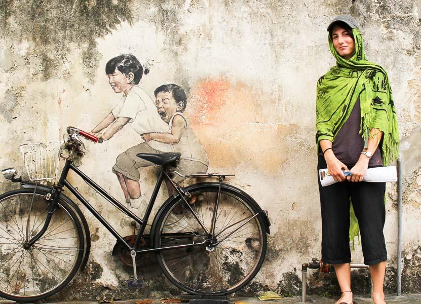Joana posando al lado de un mural en Georgetown de dos niños en bicicleta.
