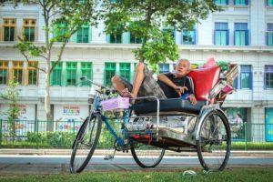 Hombre en su bici para transportar gente descansando.