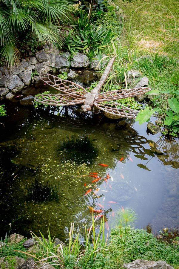 Escultura de libélula sobre lago en el Jardín Botánico Alameda.