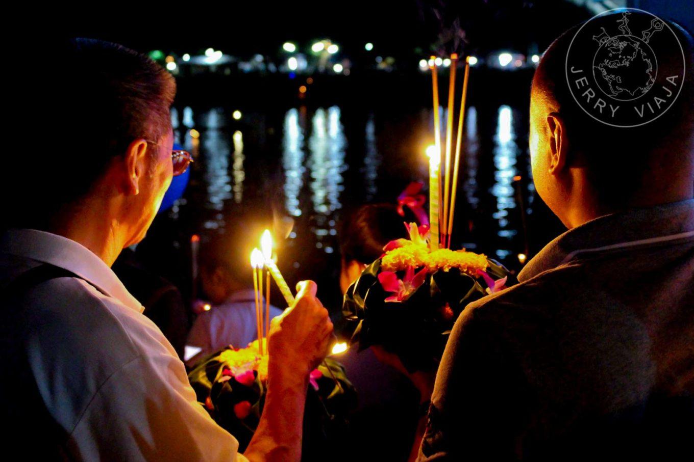 Festivales Boun Awk Pansa y Boun Suang Heua. Dos laosianos encendiendo las velas de sus coronas florales para dejar en el río Mekong durante el Boun Awk Pansa Festival