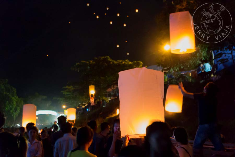Personas liberando linternas de papel encendidas al cielo.