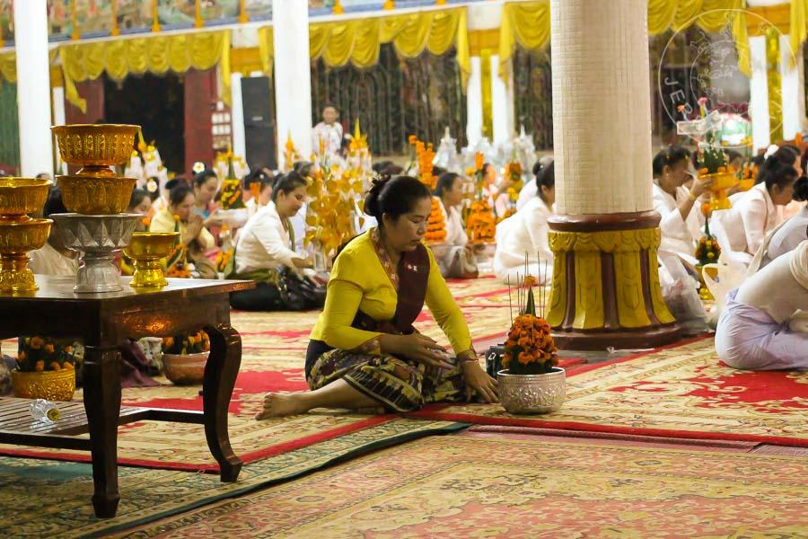 Mujer en el festival de pakse otorgando ofrendas durante las oraciones en el templo budista